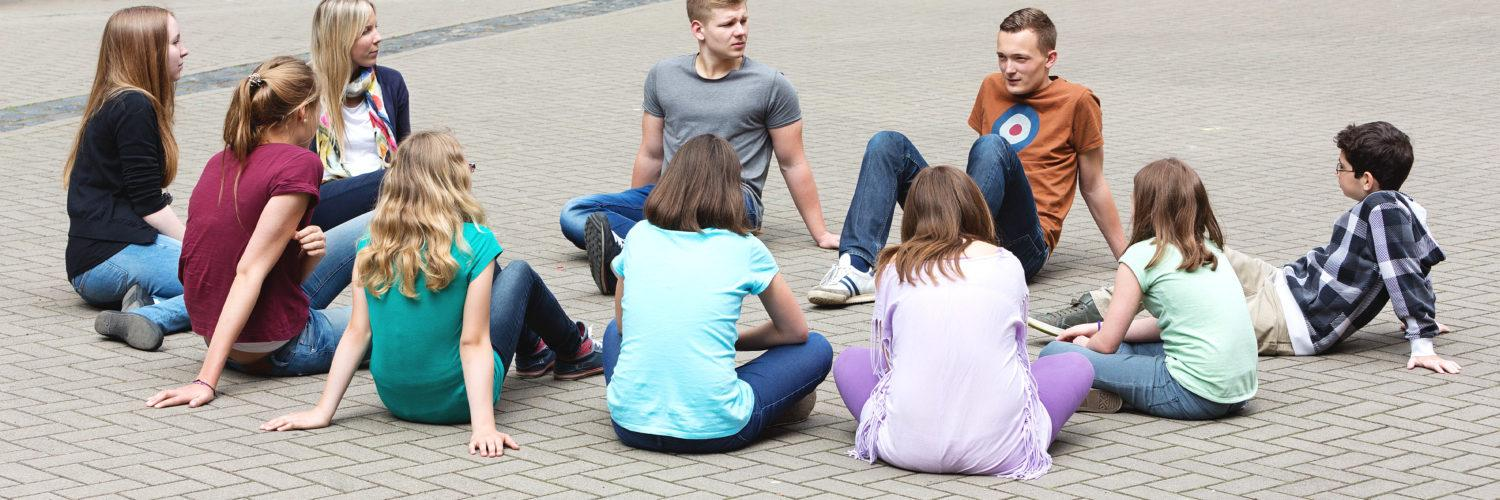 Bunch of young people sitting in a circle and talking to each others.