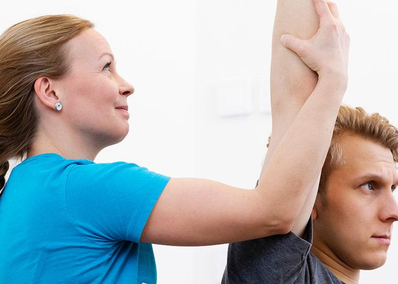 Female physiotherapist is making a passive stretch for a male customer during physiotherapy
